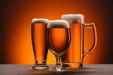 close up view of arrangement of glasses of beer on orange backdrop