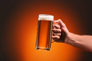 cropped shot of man holding mug of cold beer on orange background