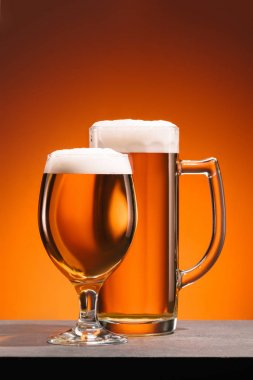 close up view of arrangement of glasses of beer with foam on orange backdrop