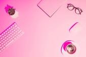 csésze kávé, növény, szemüvegek, üres tankönyv, számítógép-billentyűzet és egér asztalon rózsaszín tónusú kép