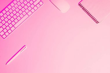 pink toned picture of computer keyboard and mouse, empty textbook and pen on table