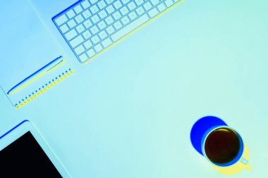 blue toned picture of coffee cup, empty textbook, pen, digital tablet and computer keyboard