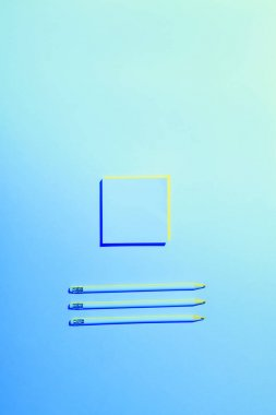 Blue toned picture of sticky note and three pencils placed in row stock vector
