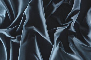 close up view of crumpled dark blue silk fabric as background