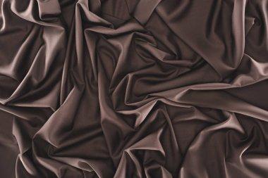 full frame of folded dark silk cloth as background