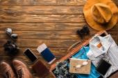 Draufsicht der Vintage Koffer mit Gepäck für die Reise auf hölzernen Tischplatte
