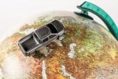 Fotografie Detailní záběr černé autíčko na zeměkouli izolované na bílém