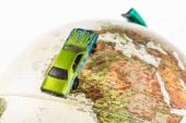 Detailní záběr zelené autíčko na zeměkouli izolované na bílém