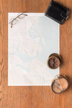 top view of map with wallet, eyeglasses and compass on wooden surface