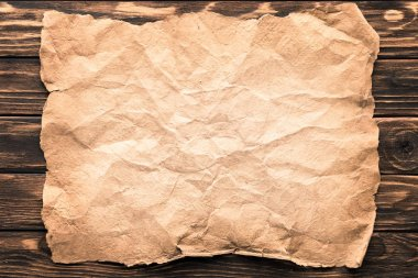 top view of blank crumpled paper on rustic wooden surface
