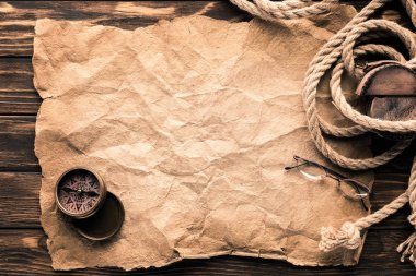 top view of blank crumpled paper with compass and rope on rustic wooden surface