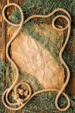 top view of blank crumpled paper with rope and fishing net