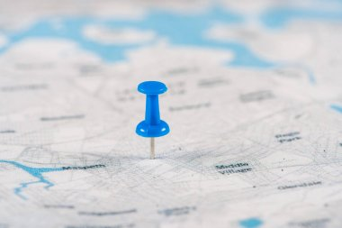 close-up shot of blue pin on travel map