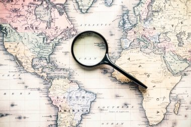 top view of magnifying glass on world map over atlantic ocean