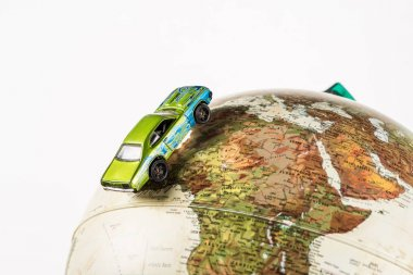 close-up shot of little toy car riding on globe isolated on white