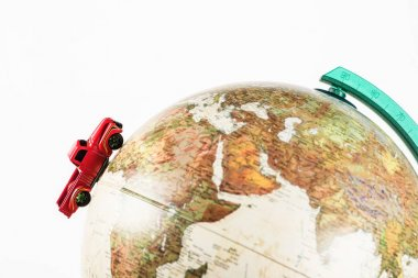 close-up shot of red toy car riding on globe isolated on white