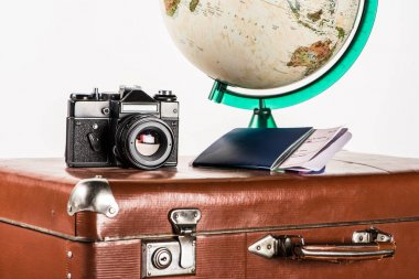 film camera with flight tickets and globe on vintage suitcase isolated on white