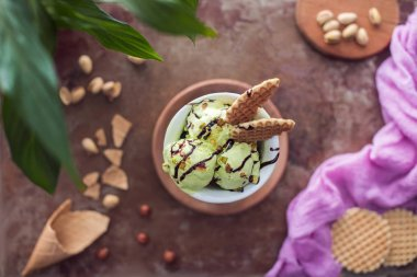 top view of delicious pistachio ice cream with waffles in glass on table