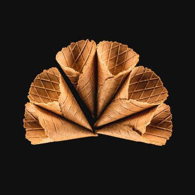 top view of delicious ice cream cones isolated on black