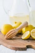 Fotografie Selektivní fokus dřevěnou paličkou a kousky citrónu na dřevěném prkénku pro výrobu limonády