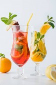 Nahaufnahme von Sommer frische Cocktails mit Erdbeere, Zitrone und orange, Minze isoliert auf weiss