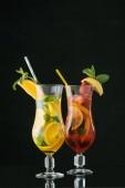 Fotografie Nahaufnahme der Sommer frische Cocktails mit Minze und Zitrusfrüchten Stücke isoliert auf schwarz