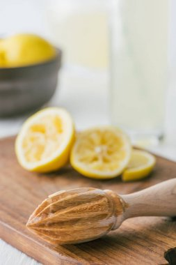 selective focus of wooden pestle and lemon pieces on wooden cutting board for making lemonade