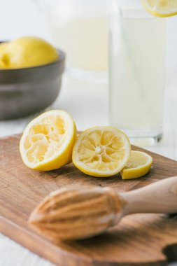 close up view of lemon pieces and wooden squeezer on cutting board for making lemonade on white tabletop