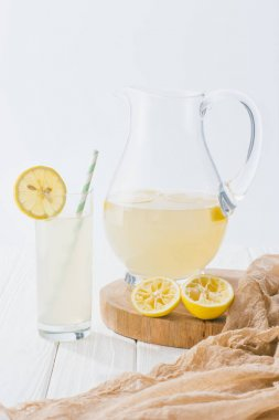 close up view of lemonade in glass with straw and jug on white wooden surface on grey backdrop