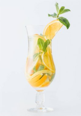 close up view of summer fresh cocktail with mint and pieces of citrus fruits isolated on white