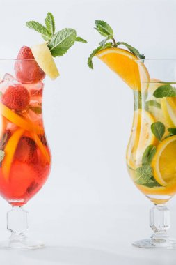 close up view of summer fresh cocktails with lemon and orange pieces, mint isolated on white