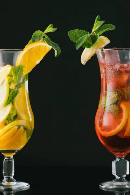 close up view of summer fresh cocktails with mint and citrus pieces isolated on black
