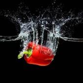 Detailní zobrazení pohybu červené papriky pádu do vody, samostatný na černém