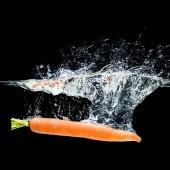 Fotografia Chiuda sulla vista di carota in acqua isolata sul nero