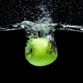 Fotografie close up view of green apple falling into water isolated on black
