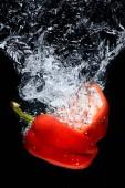 Fotografia Chiuda sulla vista di pezzi di peperone in acqua isolata sul nero