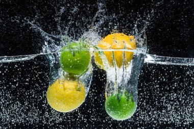 close up view of fresh lemons and limes in water isolated on black