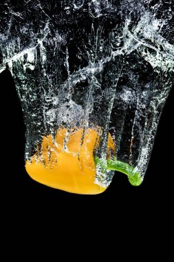 close up view of motion of yellow bell pepper falling into water isolated on black