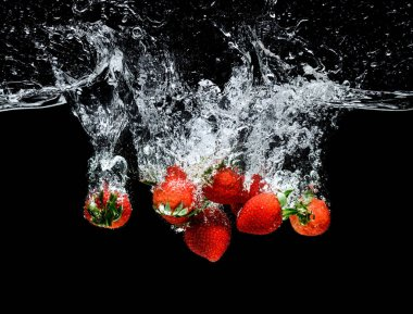 Close up view of motion of ripe strawberries falling into water isolated on black stock vector