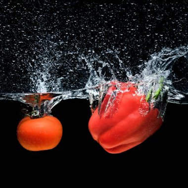 close up view of bell pepper and tomato falling into water isolated on black