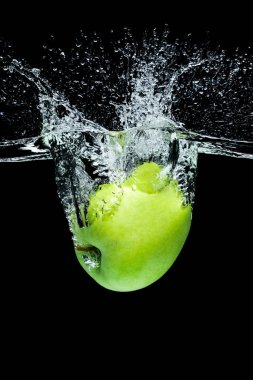 close up view of green apple falling into water isolated on black