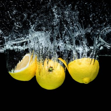 close up view of fresh lemons in water with splashes isolated on black