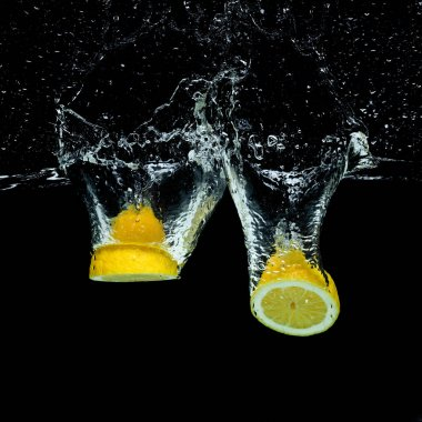 Close up view of fresh lemon pieces in water with splashes isolated on black stock vector