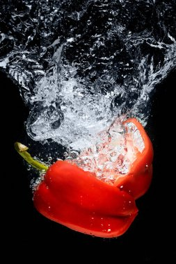 close up view of bell pepper pieces in water isolated on black