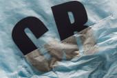schwarze Buchstaben c und r in Papier getaucht, das Wasser auf grauem Hintergrund symbolisiert