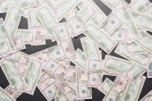 top view of scattered dollar banknotes on grey background
