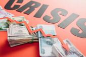 Schwarzwort Krise und Rezessionspfeil auf Euro-, Dollar- und Rubel-Banknoten auf rotem Hintergrund mit Beleuchtung