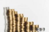 selektiver Fokus gestapelter Silber- und Goldmünzen auf der Oberfläche mit Reflexion isoliert auf Weiß