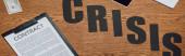 top view of word crisis, szerződés vágólapra és dollár bankjegy fa asztalra, panoráma felvétel