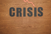 Draufsicht auf schwarzes Papier geschnitten Wort Krise und Rezession Pfeil auf Holzoberfläche mit Kopierraum